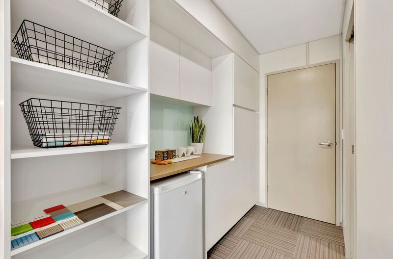 View of hallway showing storage, fridge and bench space
